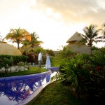 Destination wedding photographer | barcelo maya tropical resort Mexico | wedding photos | bride dancing by the pool with a sunset in the background
