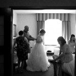 Calgary wedding photographer | Bride getting dress done up by mom and dad