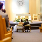 Calgary wedding photographer | Holy spirit catholic church wedding | Bride and groom sitting down in front of alter