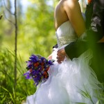 Calgary wedding photographer | Fish Creek Park wedding photos | Groom holding flowers and hugging bride in birch trees