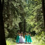 Calgary wedding photographer | Fish Creek Park wedding photos | Bride and bridesmaids walking down dirt path in tall trees