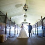 Calgary wedding photographer | Spruce Meadows wedding photos | Bride and groom walking down a horse stable