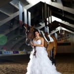 Calgary wedding photographer | Spruce Meadows wedding photos | Bride standing with a horse in a warmup ring