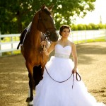 Calgary wedding photographer | Spruce Meadows wedding photos | Bride posing with a horse outside, under a tree in front of a white fence